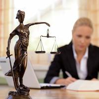 Eine junge Rechtsanwältin sitzt an ihrem Schreibtisch im Büro